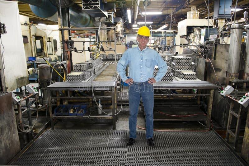 Travail de sourire d'homme, usine industrielle de fabrication photographie stock