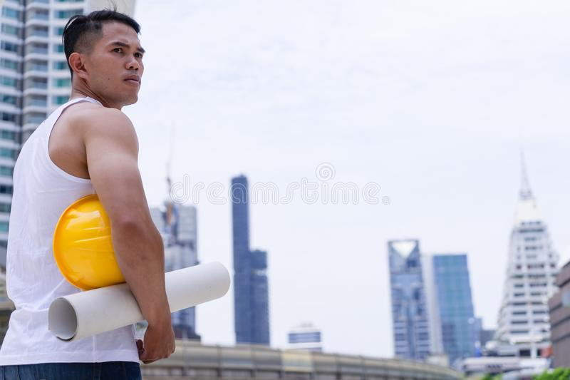Travail de travailleur d'homme dans le chantier de construction tenant le casque dur jaune photos stock