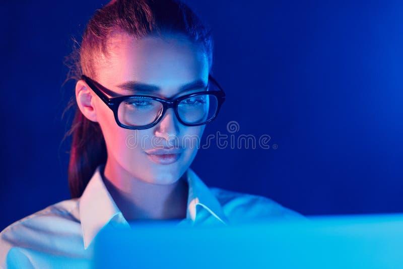 Travail en ligne de nuit Femme à l'aide de l'ordinateur portable dans les lampes au néon colorées photo stock