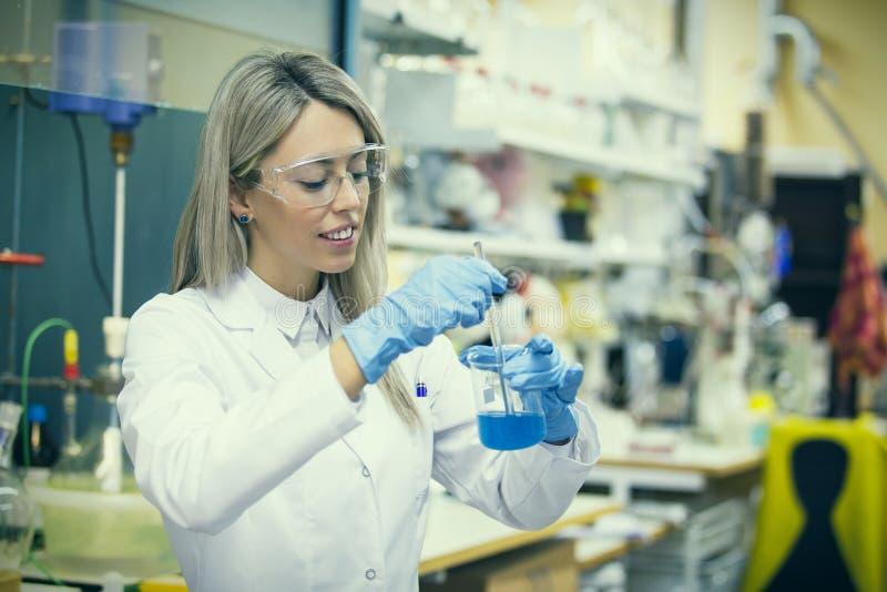 Travail femelle dans le laboratoire de chimie photo stock