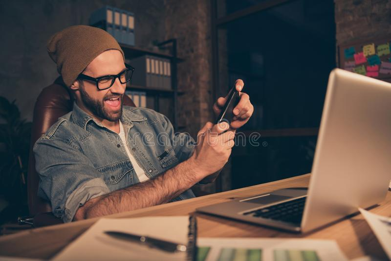 Travail frais de type au temps foncé passant le temps libre jouant le jeu de téléphone pour utiliser l'équipement occasionnel pou photographie stock