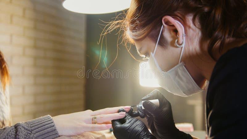Travail manuel - manucure professionnel - clouez le maître dans le masque médical faisant la manucure professionnelle, se ferment photographie stock libre de droits