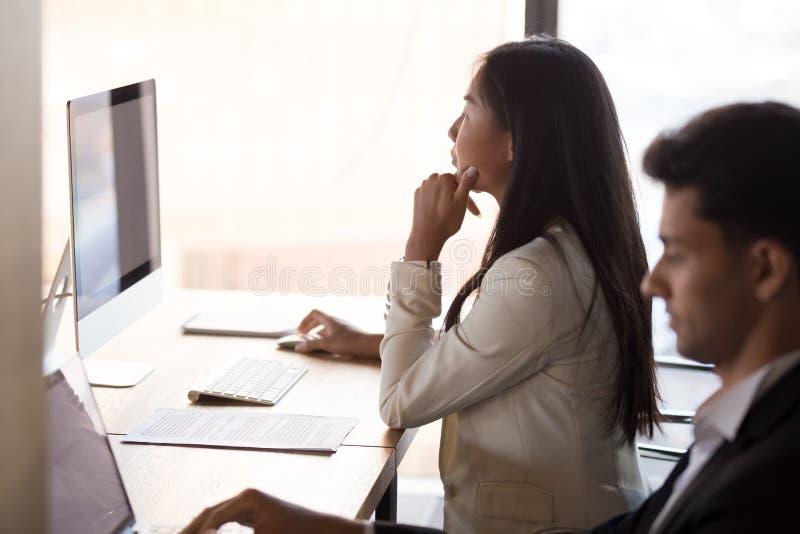 Travail occupé focalisé des employés asiatiques au PC dans l'espace coworking images libres de droits