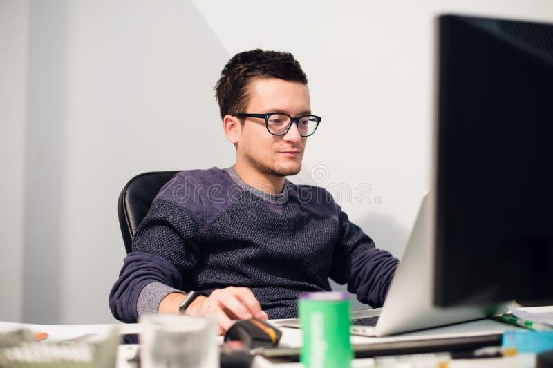 Travail occupé Verres de port de jeune homme bel songeur sur l'ordinateur portable tout en se reposant à son lieu de travail photo libre de droits