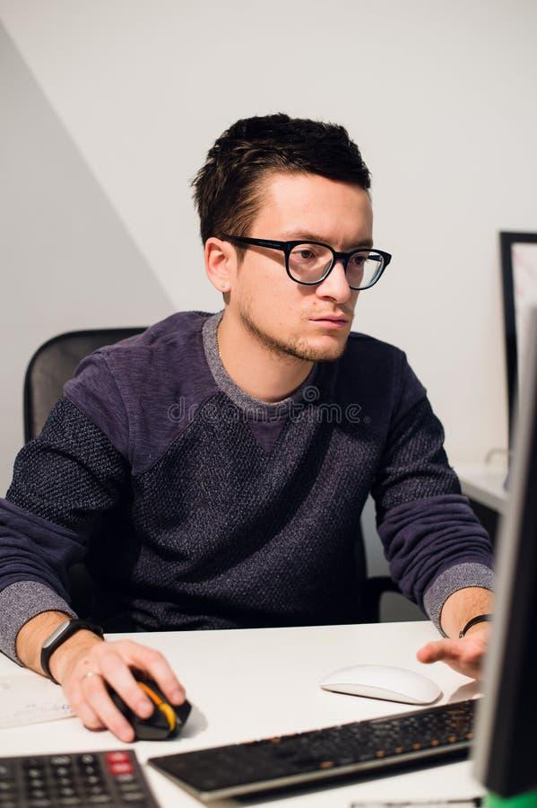 Travail occupé Verres de port de jeune homme bel songeur sur l'ordinateur portable tout en se reposant à son lieu de travail images stock