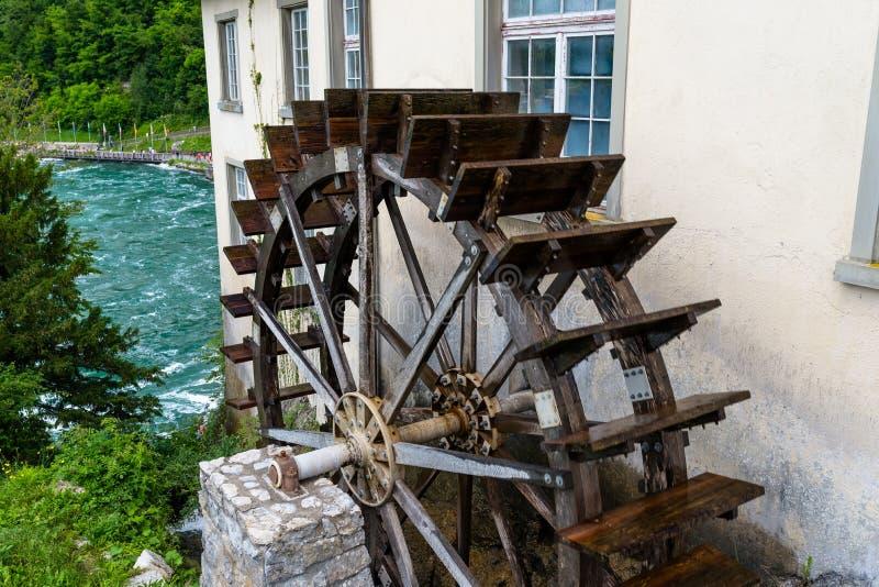 Travaillant un en bois, roue d'eau pour convertir l'énergie de l'écoulement de l'eau, au début du Rhin en Suisse image libre de droits
