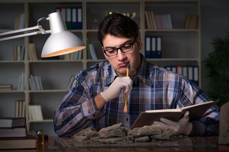 Travailler d'archéologue de fin de nuit dans le bureau image stock