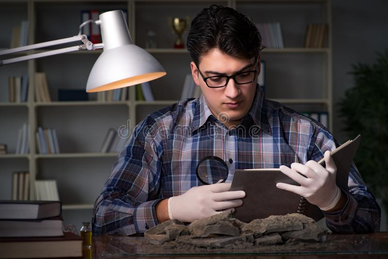 Travailler d'archéologue de fin de nuit dans le bureau images libres de droits