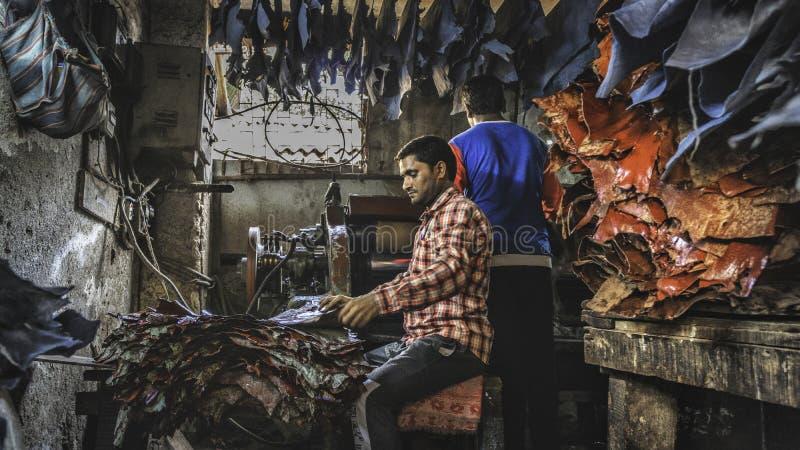 Travailler de jeune homme dur dans l'usine en cuir à l'intérieur du taudis de dharavi dans mumbay photographie stock libre de droits