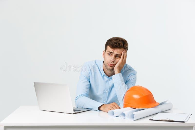 Travailler occupé focalisé d'ingénieur assidu sérieux sur le grand projet architectural tard, se reposant à son espace de travail photographie stock libre de droits