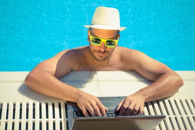 Travailler sur l'ordinateur portable de la piscine photos libres de droits