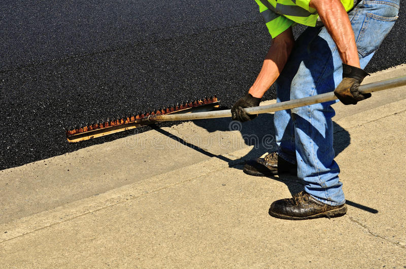 Travailleur à l'aide d'un râteau pour pousser l'asphalte excédentaire images libres de droits
