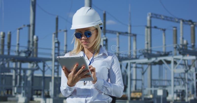 Travailleur électrique féminin de sourire sur un comprimé image libre de droits