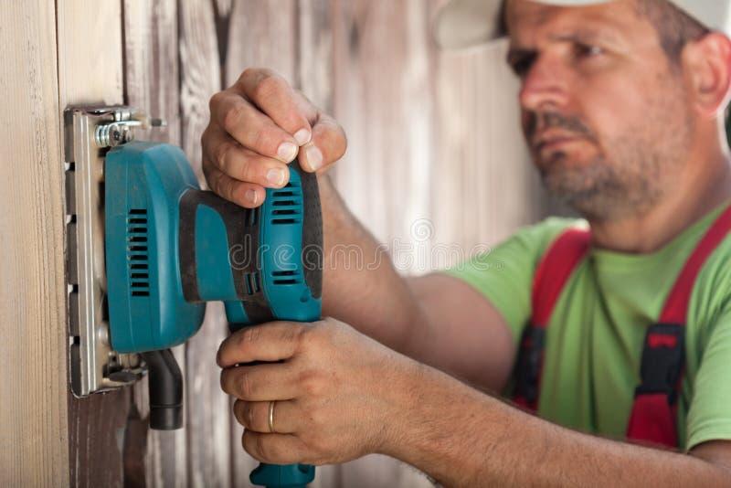 Travailleur éraflant la surface en bois verticale avec la ponceuse vibrante - photo libre de droits