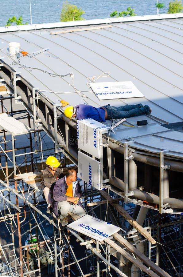Travailleur étranger travaillant à l'installation de toit photographie stock