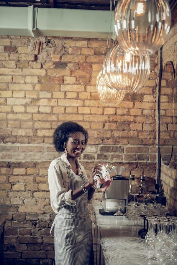 Travailleur afro-américain beau de barre s'engageant en verres polissant à la barre image libre de droits