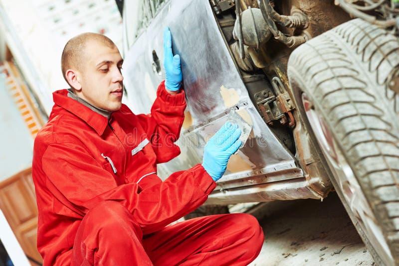Travailleur appliquant le mastic de réparation de carrosserie photo stock