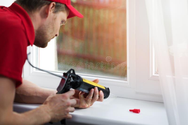Travailleur appliquant le mastic de silicone sous le châssis de fenêtre image stock