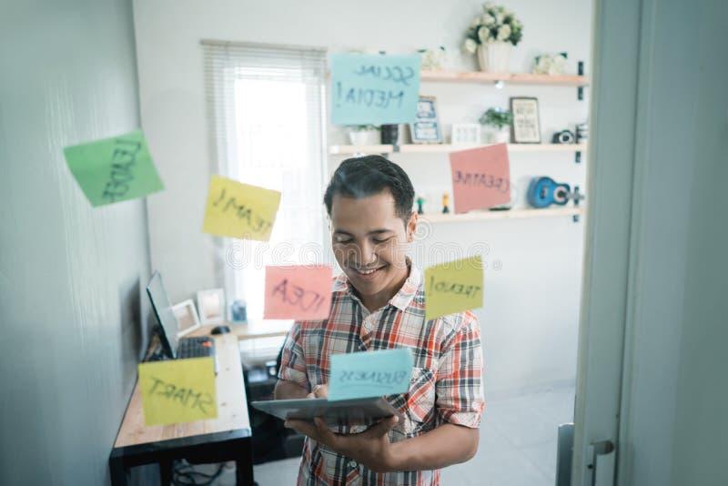 Travailleur asiatique dactylographiant sur un comprimé numérique au rappel le noyau de se réunir photos stock