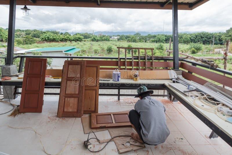 Travailleur asiatique reconstruit et fenêtre de peinture photo stock