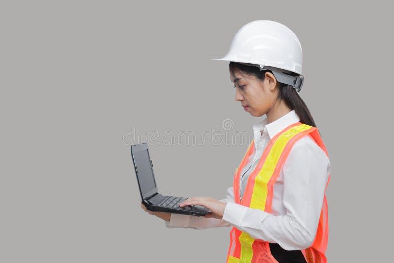 Travailleur asiatique sûr de beauté jeune avec l'ordinateur portable de transport d'équipement safty sur le fond d'isolement gris photos stock