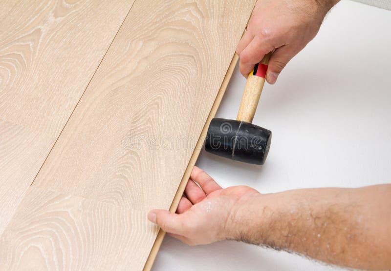 Travailleur assemblant le plancher en stratifié utilisant un marteau photos stock