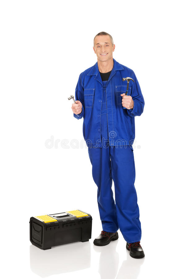 Travailleur avec la boîte à outils montrant sa clé et marteau photographie stock