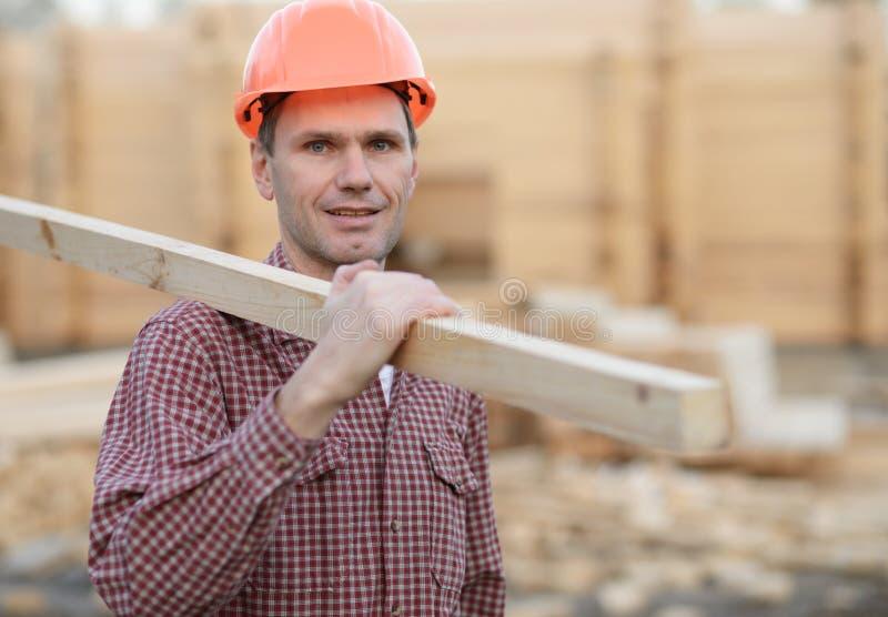 Travailleur de la construction avec la planche photos stock