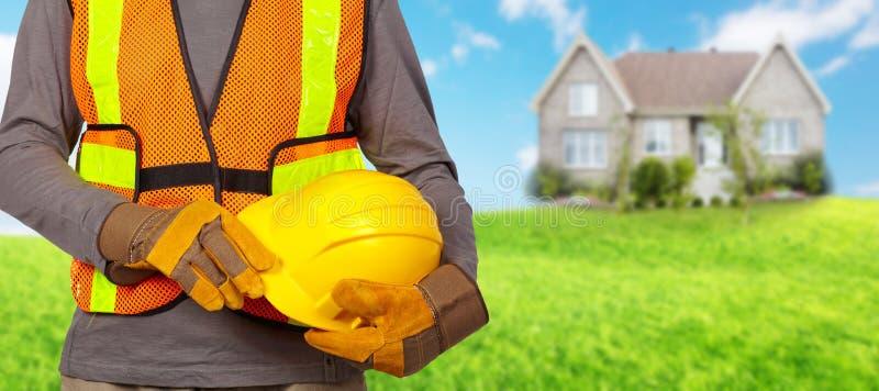 Travailleur avec le casque dans le gilet orange de sécurité photographie stock