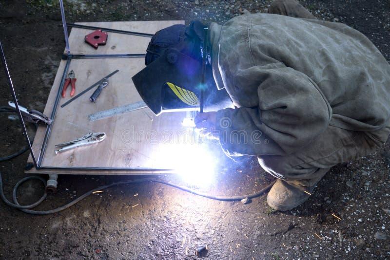 Travailleur avec le métal de soudage de masque protecteur dans la diffusion de milieu industriel et d'étincelles photos libres de droits