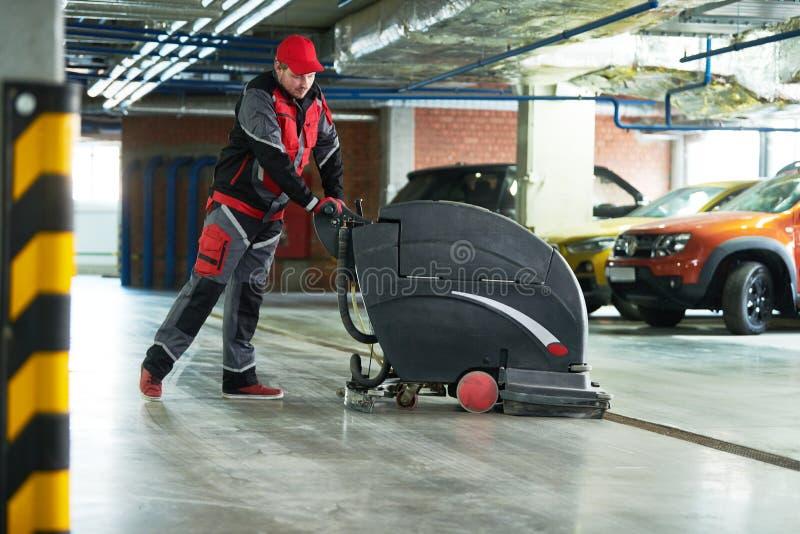 Travailleur avec le plancher de nettoyage de machine dans le garage photos stock