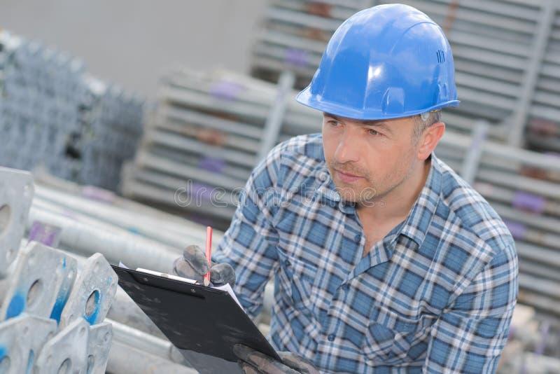 Travailleur avec le presse-papiers regardant des poteaux d'échafaudage photo stock
