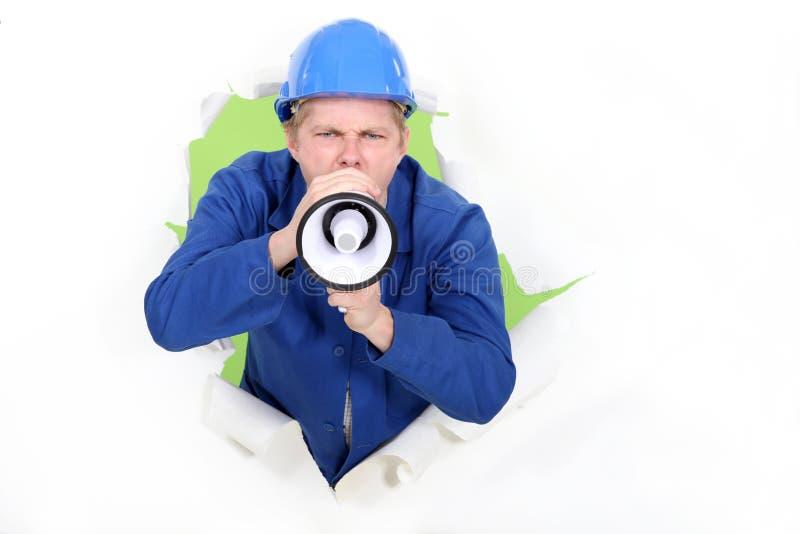 Travailleur avec un mégaphone. photographie stock libre de droits