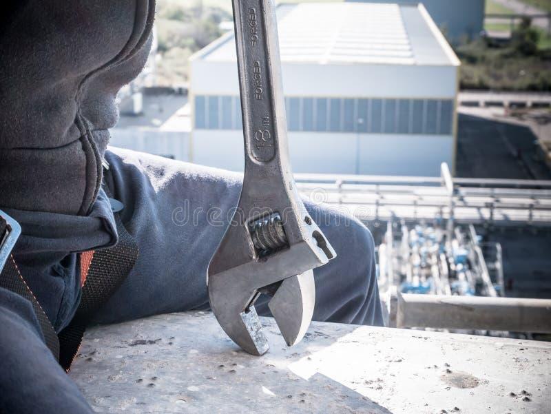 Travailleur avec une clé à la haute altitude photographie stock libre de droits