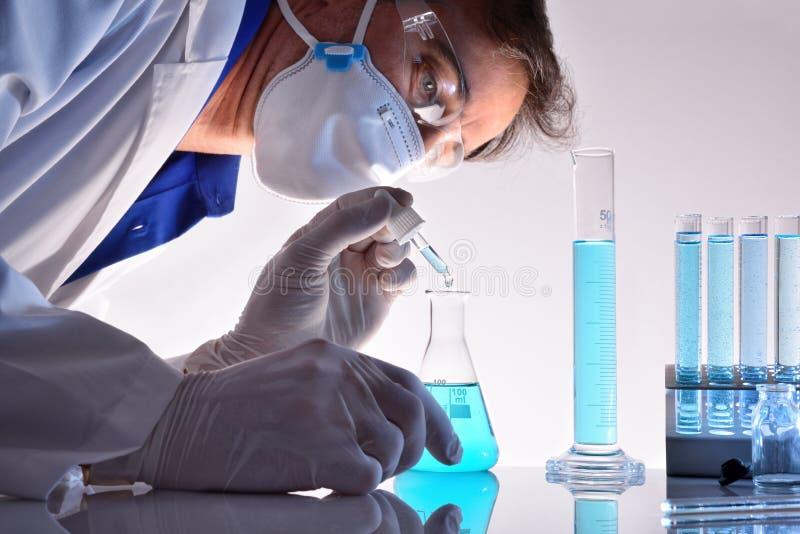Travailleur chimique examinant différentes substances dans le laboratoire photos stock