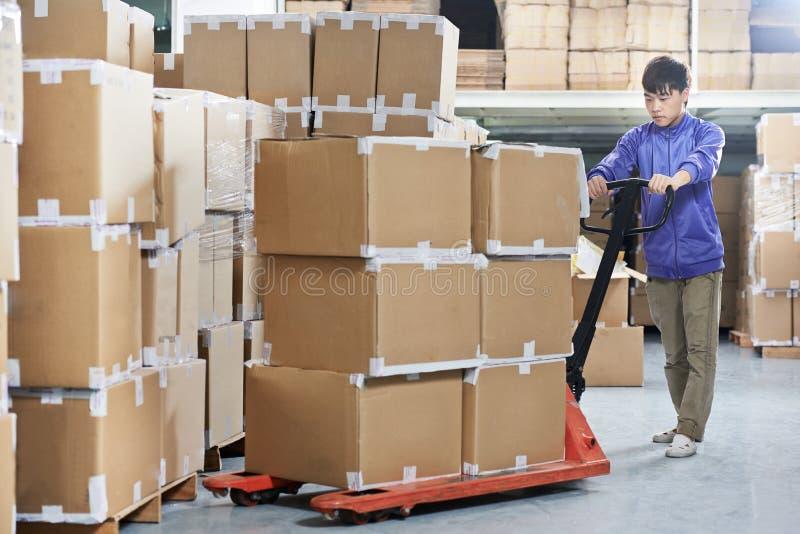 Travailleur chinois d'entrepôt avec l'empileur de chariot élévateur image libre de droits