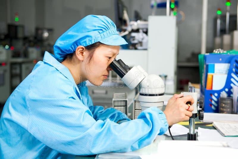 Travailleur chinois sur le microscope de contrôle d'usine photo stock