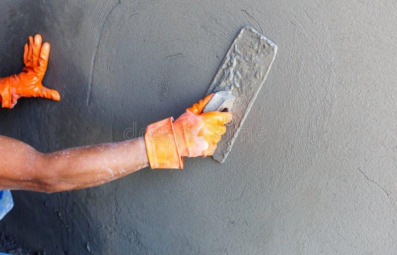 Travailleur concret de plâtrier au mur de la construction de maison image libre de droits