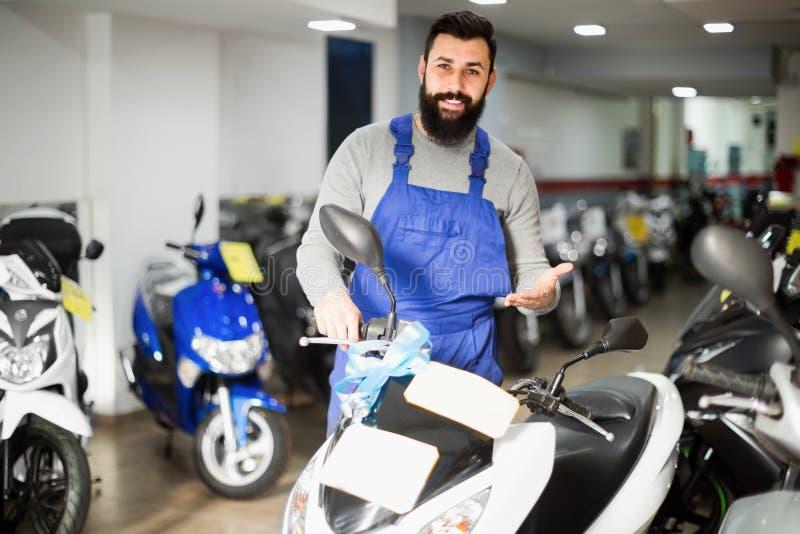 Travailleur démontrant des motos et des scooters photos libres de droits