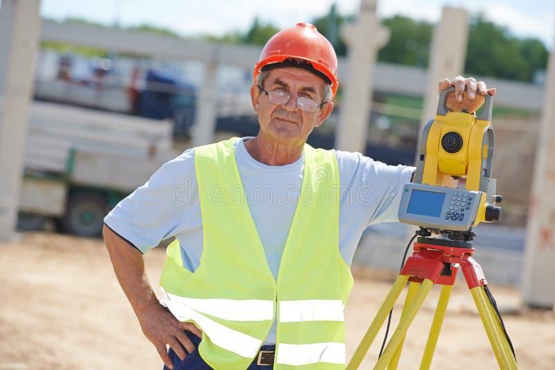 Travailleur d'arpenteur avec le théodolite images libres de droits