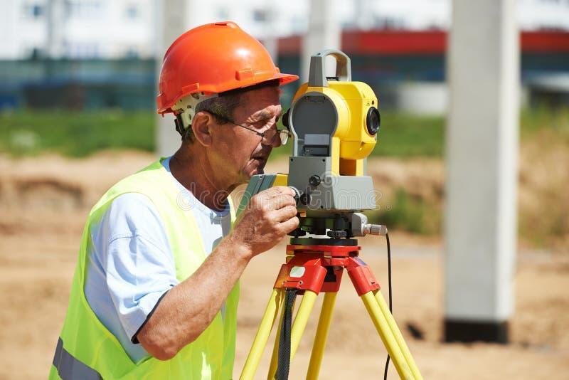 Travailleur d'arpenteur avec le théodolite image libre de droits