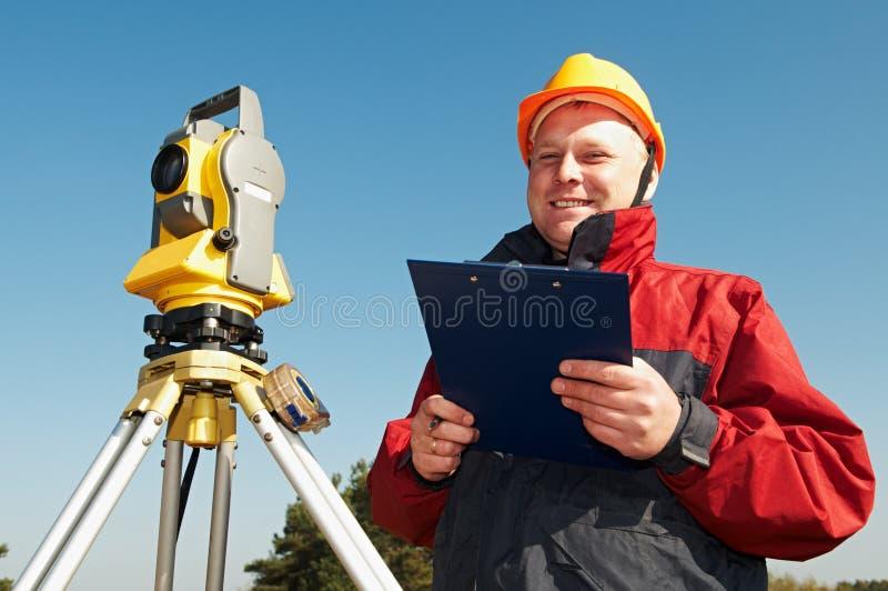 Travailleur d'arpenteur avec le théodolite photo libre de droits
