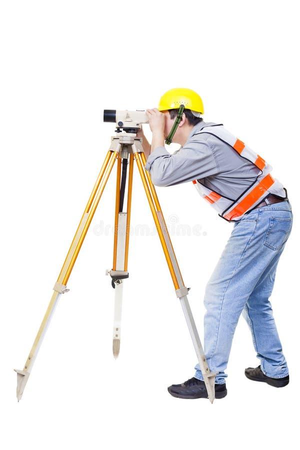 Travailleur d'arpenteur faisant la mesure et d'isolement images libres de droits