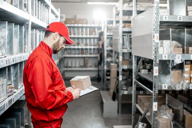 Travailleur d'entrepôt avec le presse-papiers dans le stockage photos libres de droits