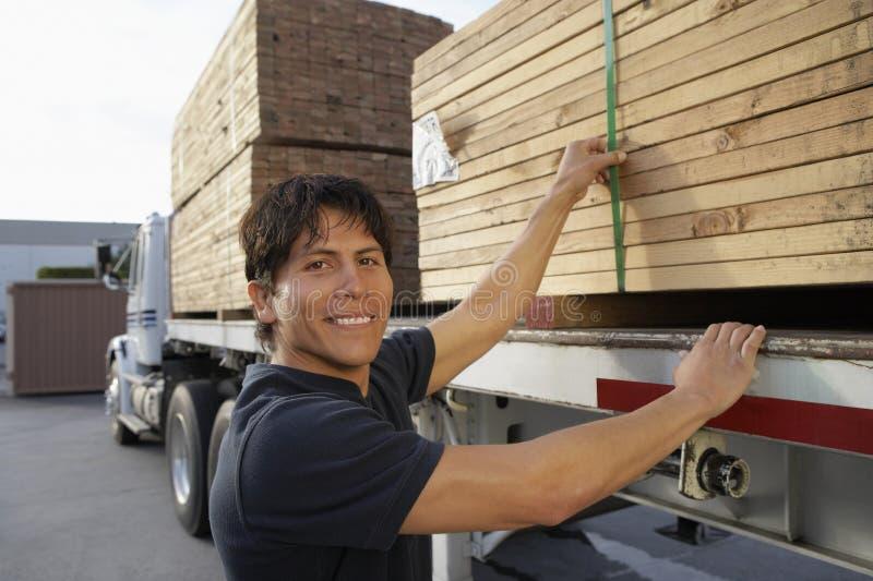 travailleur d 39 entrep t chargeant les planches en bois sur le transporteur de camion image stock. Black Bedroom Furniture Sets. Home Design Ideas