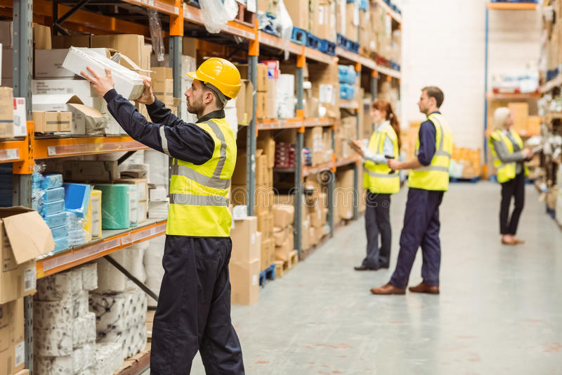 Travailleur d'entrepôt prenant le paquet dans l'étagère image libre de droits