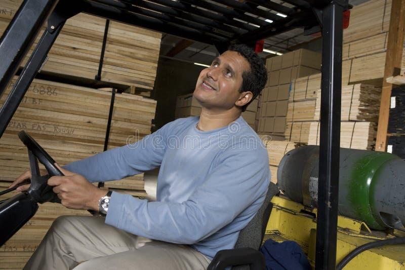 Travailleur d'entrepôt s'asseyant dans le chariot élévateur et recherchant image stock