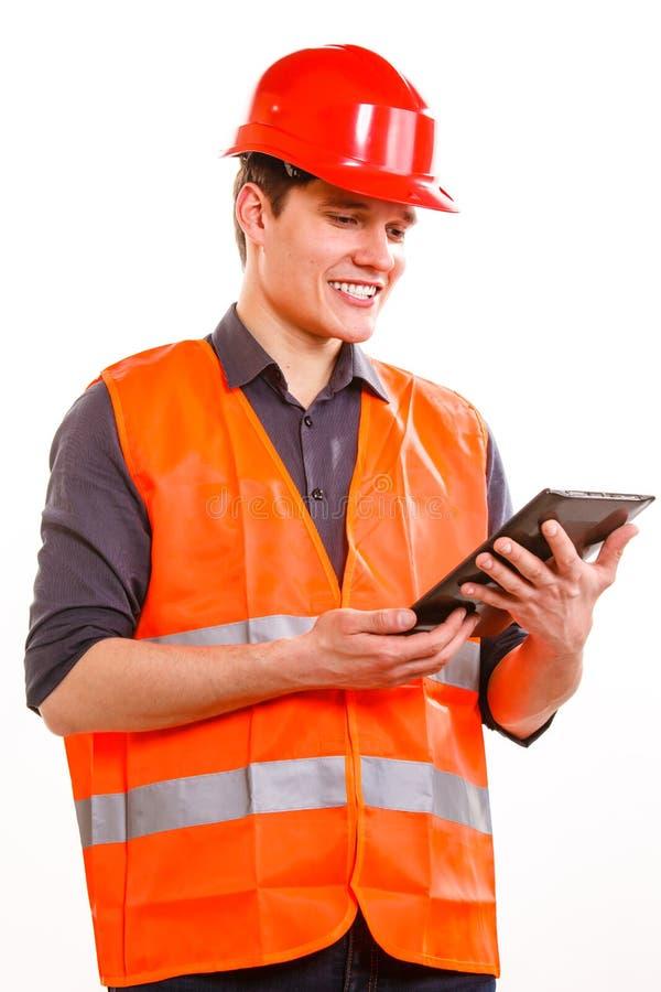 Travailleur d'homme dans le casque antichoc de gilet de sécurité utilisant le comprimé photographie stock libre de droits