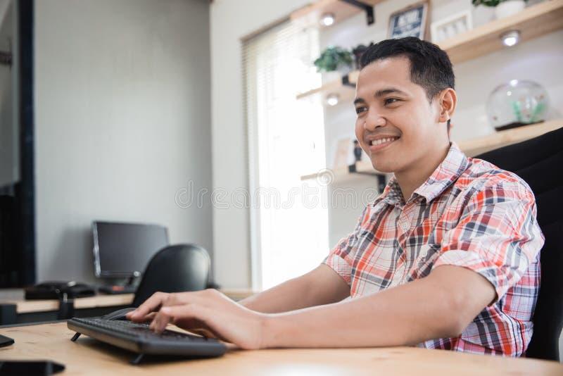 Travailleur d'homme travaillant dans l'ordinateur avant photographie stock