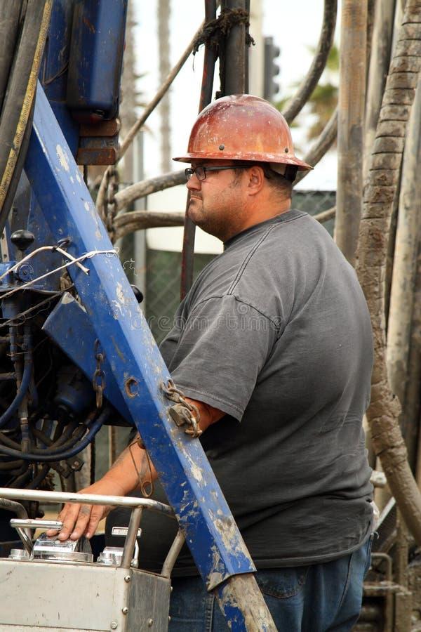 Travailleur d'huile au puits de pétrole abandonnant le chantier photo stock